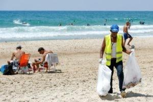 Un employé de la municipalité de Herzliya (Israël) collecte des déchets sur la plage, le 21 juin 2019 © AFP JACK GUEZ