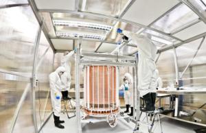 Scientifiques de la collaboration XENON1T travaillant dans une salle propre à l'assemblage du matériel constituant le cœur du détecteur (chambre à projection temporelle) de l'expérience