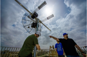 Installing the satellite dish that will receive the data transmitted from BGUSAT and send it to the ground station at BGU's EPIF. Aviran Sadon, a doctoral student who was instrumental in the BGUSAT process, is pictured gesturing in this photo from March 2016.