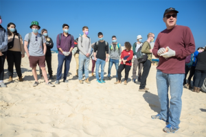 Volunteers from Ben-Gurion University, including President Prof. Daniel Chamovitz (foreground), clean up tar from the Nitzanim beach recently after the catastrophic oil spill in the Mediterranean Sea off the coast of Israel